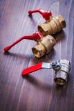 Tre dispositivi degli idraulici con le maniglie rosse sopra Fotografie Stock