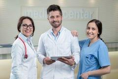 Tre doktorer som använder en minnestavla i ett ljust kontor Arkivbild
