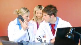 Tre doktorer som arbetar i sjukhuskontorslängd i fot räknat arkivfilmer
