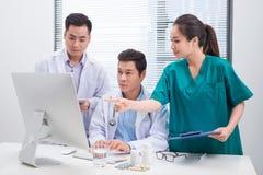 Tre doktorer som diskuterar tålmodiga mappar på kontor arkivbilder