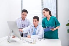 Tre doktorer som diskuterar tålmodiga mappar på kontor arkivbild