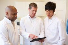 Tre doktorer som har diskussion genom att använda den Digital minnestavlan Arkivbilder