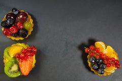 Tre dolci con i bio- frutti freschi, arancia, kiwi, fragole, mirtilli, ribes rosso, uva, lamponi, more, foto fotografia stock