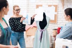 Tre donne alla fabbrica dell'indumento Stanno discutendo la progettazione di nuovo vestito immagini stock libere da diritti