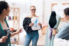 Tre donne alla fabbrica dell'indumento Stanno discutendo la progettazione di nuovo vestito immagini stock