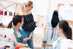 Tre donne alla fabbrica dell'indumento Stanno discutendo la progettazione per il nuovo vestito fotografie stock libere da diritti