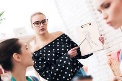 Tre donne alla fabbrica dell'indumento Stanno discutendo la progettazione per il nuovo vestito immagine stock