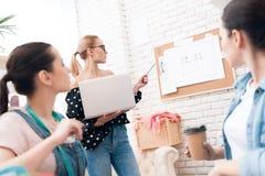 Tre donne alla fabbrica dell'indumento Stanno discutendo la progettazione per il nuovo vestito fotografia stock