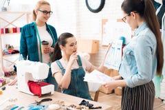 Tre donne alla fabbrica dell'indumento Stanno esaminando i modelli fotografia stock