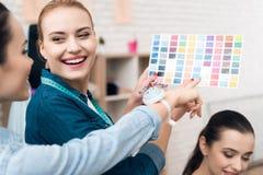 Tre donne alla fabbrica dell'indumento Stanno esaminando i modelli di colore per il nuovo vestito immagine stock libera da diritti