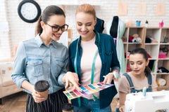 Tre donne alla fabbrica dell'indumento Stanno esaminando i modelli di colore per il nuovo vestito immagini stock libere da diritti