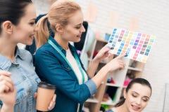 Tre donne alla fabbrica dell'indumento Stanno esaminando i modelli di colore per il nuovo vestito immagini stock