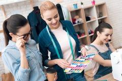 Tre donne alla fabbrica dell'indumento Stanno esaminando i modelli di colore per il nuovo vestito fotografia stock libera da diritti