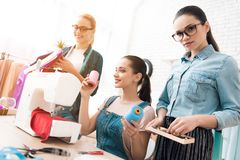 Tre donne alla fabbrica dell'indumento Stanno scegliendo i bottoni per il vestito immagini stock libere da diritti