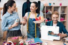 Tre donne alla fabbrica dell'indumento Stanno scegliendo il colore del filo per il nuovo vestito fotografie stock