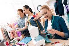 Tre donne alla fabbrica dell'indumento Stanno scegliendo il colore del filo per il nuovo vestito fotografie stock libere da diritti