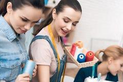 Tre donne alla fabbrica dell'indumento Stanno scegliendo il colore del filo per il nuovo vestito immagini stock libere da diritti