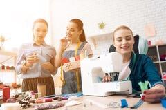 Tre donne alla fabbrica dell'indumento Stanno scegliendo il colore del filo per il nuovo vestito immagine stock