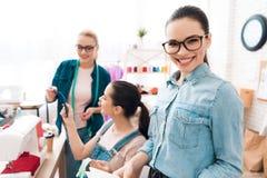 Tre donne alla fabbrica dell'indumento Stanno scegliendo le chiusure lampo per il vestito immagine stock
