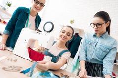 Tre donne alla fabbrica dell'indumento Stanno scegliendo le chiusure lampo per il vestito fotografia stock