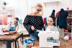Tre donne alla fabbrica dell'indumento Stanno sedendo dietro le macchine per cucire fotografia stock libera da diritti