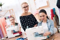 Tre donne alla fabbrica dell'indumento Stanno sedendo dietro le macchine per cucire fotografia stock