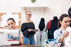 Tre donne alla fabbrica dell'indumento Stanno sedendo dietro le macchine per cucire fotografie stock