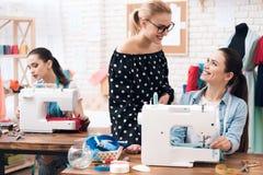 Tre donne alla fabbrica dell'indumento Stanno sedendo dietro le macchine per cucire immagini stock libere da diritti