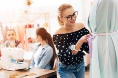 Tre donne alla fabbrica dell'indumento Stanno sedendo dietro le macchine per cucire e stanno prendendo le misure di nuovo vestito immagini stock