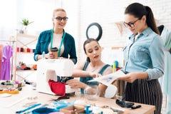 Tre donne alla fabbrica dell'indumento Uno di loro che mostrano modello immagine stock