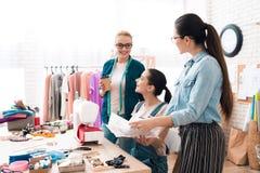 Tre donne alla fabbrica dell'indumento Uno di loro che mostrano modello immagini stock libere da diritti