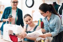 Tre donne alla fabbrica dell'indumento Uno di loro che mostrano modello fotografia stock