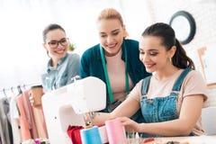 Tre donne alla fabbrica dell'indumento Uno di loro sta cucendo il nuovo vestito immagine stock