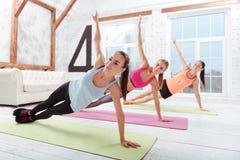 Tre donne attive che godono dello sport nello studio di forma fisica Immagini Stock