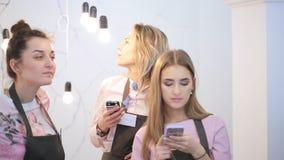 Tre donne belle, vestite negli stessi grembiuli verde scuro, stanno nello studio di arte stock footage