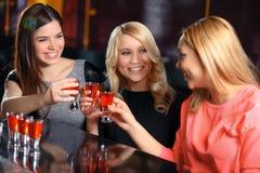 Tre donne bevono nella barra Immagini Stock