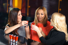 Tre donne bevono nella barra fotografia stock libera da diritti