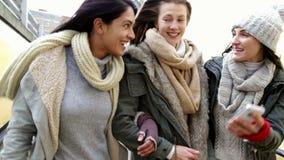 Tre donne che esaminano uno smartphone come camminano insieme stock footage