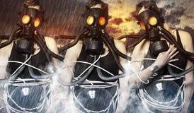 Tre donne che indossano le maschere antigas su fondo apocalittico Immagini Stock