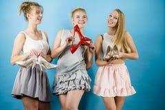 Tre donne che mostrano le scarpe dei tacchi alti Immagini Stock