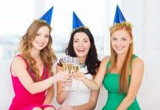 Tre donne che portano i cappelli con i vetri del champagne Immagini Stock Libere da Diritti