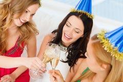 Tre donne che portano i cappelli con i vetri del champagne Immagini Stock