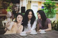Tre donne che prendono foto nel caffè Immagini Stock