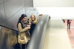 Tre donne che si alzano sulla scala mobile Fotografia Stock