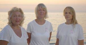 Tre donne con i nastri rosa di consapevolezza del cancro al seno stock footage