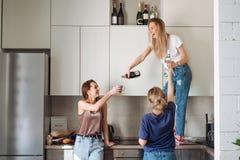 Tre donne con le bottiglie di alcool fotografie stock