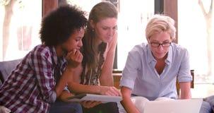 Tre donne di affari che hanno riunione informale in ufficio stock footage