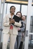 Tre donne di affari che lasciano un edificio per uffici. Immagine Stock