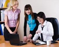 Tre donne di affari graziose comunicano in ufficio immagine stock