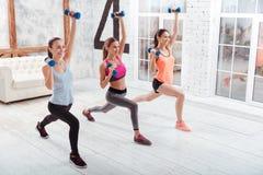 Tre donne esili che fanno gli affondo nello studio di forma fisica Fotografia Stock Libera da Diritti